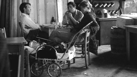 Leonard Cohen, Marianne Ihlen and friend sitting in Cohen's home in Hydra, Greece. Baby Axel is in a