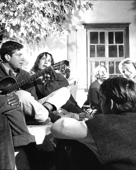 Canadian poet, author, and musician Leonard Cohen (second left) plays guitar under a tree with, amon