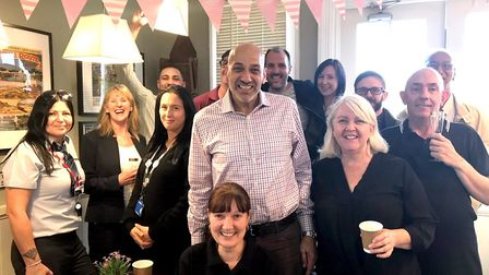 Hassan Atta and his wife Kate (centre, standing) celebrate the official opening of Rico's Coffee at