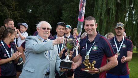 Cllr Gordon Thorpe handing over the cup to the winning team - the Wyton Warriers