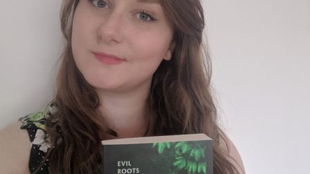 University of Hertfordshire student Daisy Butcher with her book Evil Roots: Killer Tales of the Bota