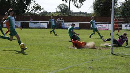 St Ives striker Ezra Forde slides towards goal at Biggleswade Town, but sadly the ball is heading th