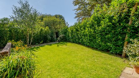 The rear garden is laid mainly to lawn with a timber summer house and a paved terrace. Picture: Stru