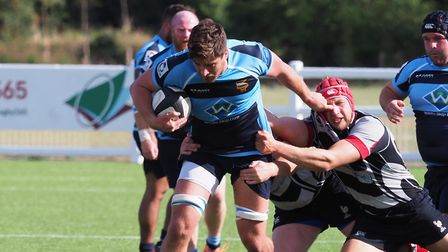 Harpenden skipper Oli Lacey attempts to get to grips with Eton Manor's Jack Sullivan. Picture: MARTI
