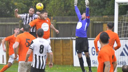 St Ives Town man Danny Kelly and Soham Town Rangers player-coach Lloyd Groves do battle in the air w