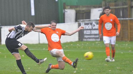 Soham Town Rangers defenders Cameron Watson is at full-stretch as St Ives Town debutant James Peters