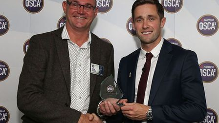 St Ives & Warboys chairman Martin Croucher receives his award from England star Chris Woakes. Pictur