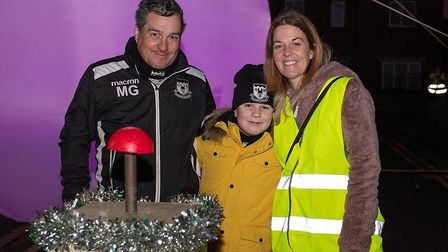 Elliot Gill (centre) aged 9 who won the raffle to turn on the Christmas Lights. He is pictured with