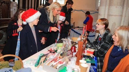 Mum, Carolyn points out some Christmas goodies to triplettes Indigo, Lottie and Harry at Ashwell Chr