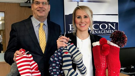 Tony Larkins and Natasha Oliver from Beacon Wealth Management with some of the Christmas socks.