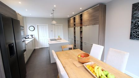 The fitted kitchen comprises a range of wall and base mounted units with Quartz stone work surfaces