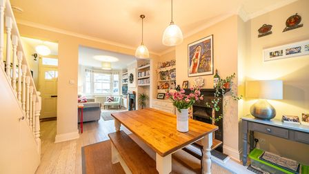 The living dining room boasts wood effect flooring, feature fireplaces, stylish radiators and fitted