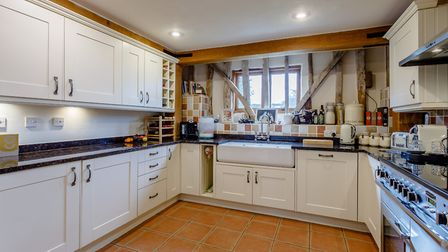 The kitchen is fitted with shaker-style units, granite stone work surfaces, twin Butler sinks and a