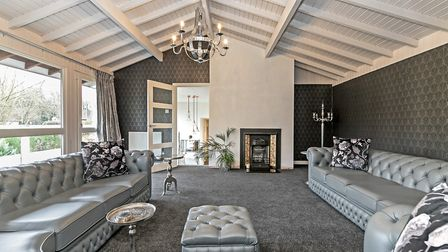 The light and spacious living room has high ceilings, large windows and a door that leads out to a f