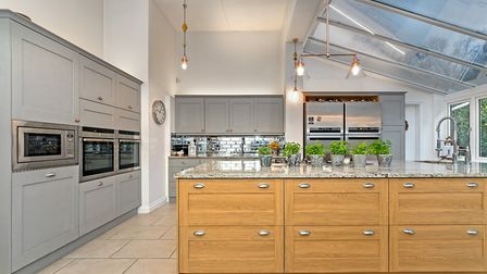 The bespoke fitted kitchen has a large breakfast island finished with granite work surfaces. Picture