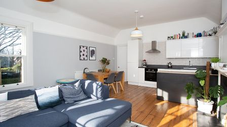 The sitting room opens to a modern kitchen area. Picture: Frost's