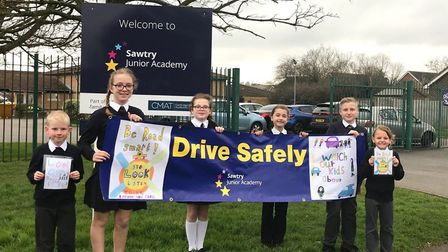 Pupils at Sawtry Junior Academy with the road safety banner outside the school. PICTURE: Athen