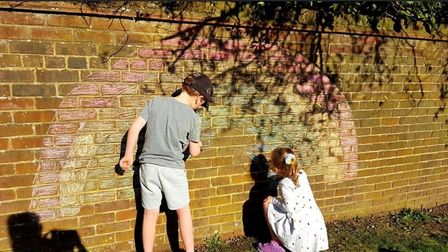 Aulay and Beatrice Lonsdale turning the garden wall into a colourful rainbow. Picture: Supplied