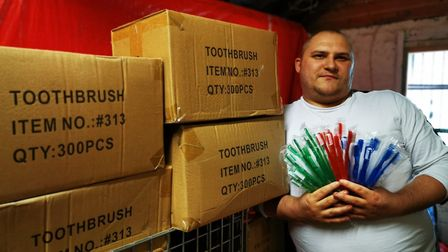 Emmaus resident Curtis Littleford in front of the toothbrushes donated to Watford General Hospital.