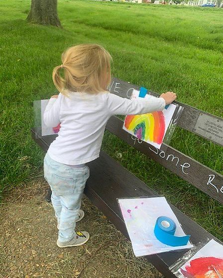 Three-year-old Beatrice displaying her artwork on a Redbourn bench which was targeted by vandals. Pi