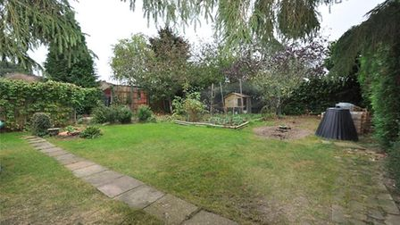 The west-facing rear garden has a variety of mature flowers, trees and shrubs. Picture: Collinson Ha