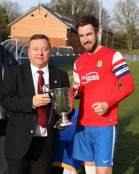 Skew Bridge captain Andy Saul receives the Herts Sunday Cup from Herts FA director Steve Trulock in