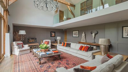One of The Barn House's stand out features is this double-height drawing room with mezzanine landing