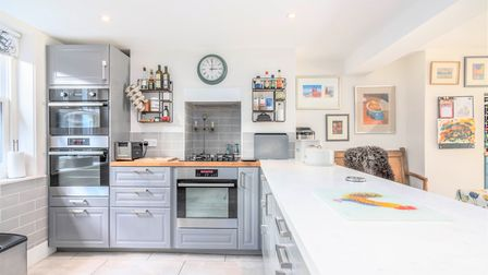 The extended fitted kitchen boasts modern fitted appliances, plentiful worktop space and underfloor