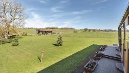 The garden offers a tranquil and spacious setting to relax in, with rolling fields and paddocks beyo