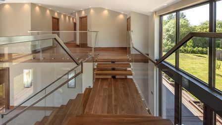 Stepping up to the first floor the staircase bears left and right, with glass balustrading on both s