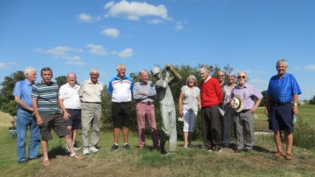 Heydon Grange Golf Club's Roy Bell (red sweater) with club members and the statue he made for the cl