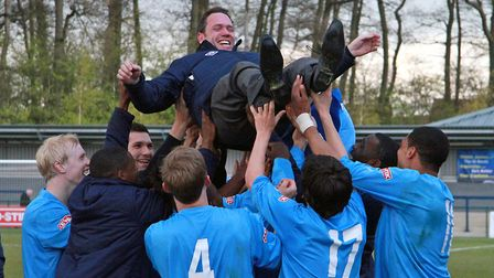 GOING UP: St Neots Town manager Dennis Greene gets the bumps from his players after the club had won