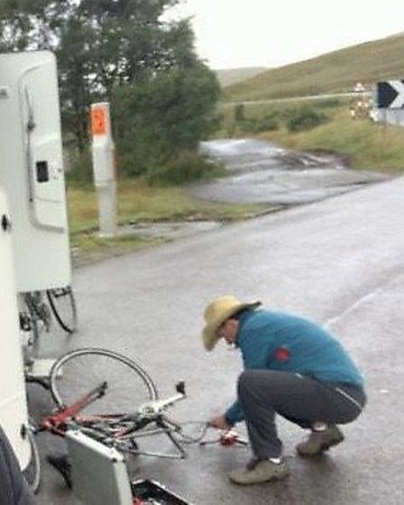 Bevan in rain swept Scotland constructing a rideable bike out of two broken bikes