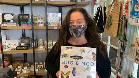 Emma Bustamante from Cositas Gifts with the Bug Bingo game bought by Ed Davey.