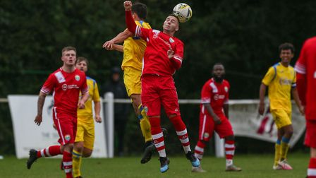 Nathan McGreevy of Harpenden Town challenges Antony Stockman of London Colney in the air in the matc
