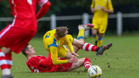 George Robinson of Harpenden Town is fouled by Ross Mercer of London Colney in the match between Ha