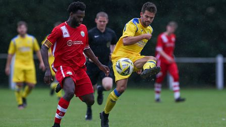 Nathan McGreevy of Harpenden Town plays a pass under pressure from Issac Olaleye of London Colney in
