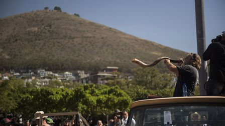 A protester blows a horn as South African farmers & farm workers attend a demonstration at the Green