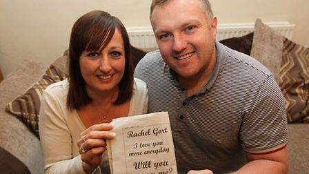 Rachel Gort and Pete Wickens at home after announcing their engagement, with the advert Pete put in