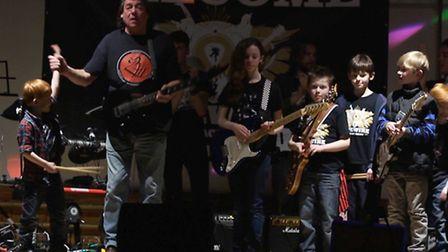 Dennis Stratton on stage with youngsters at the concert