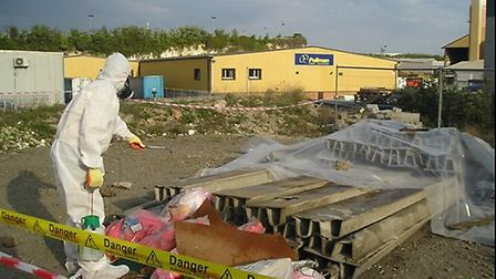 An Environment Agency officer assessing asbestos waste dumped in Essex