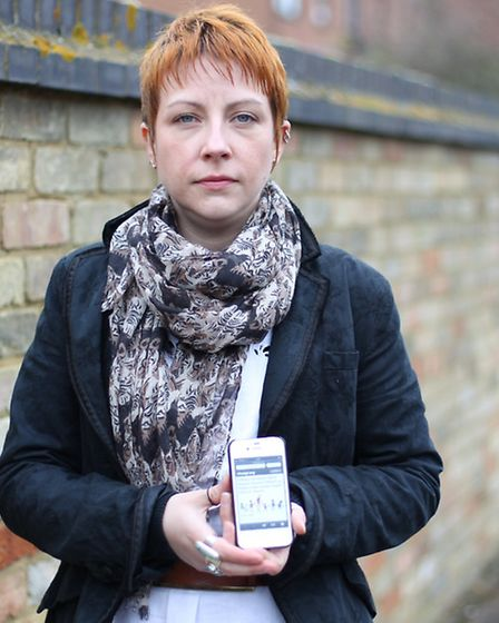 Monique Blackham, pictured with the petition on her phone, helped set up a petition calling for NHDC