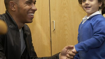Lewis Hamilton meets pupil Louie Titre during a return visit to Peartree Infant and Junior School
