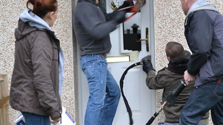 Police officers force entry into a Hitchin property