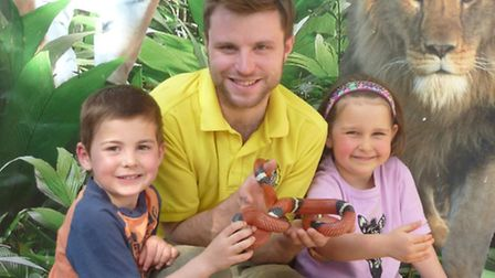 Livia Bass, age 4, and Scott Simpson, 5, with keeper Mikey Peck and Dennis the Sinoloan Milksnake