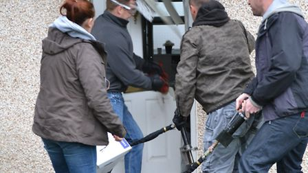 Police officers force entry into a Hitchin property during the raids, where three people were arrest