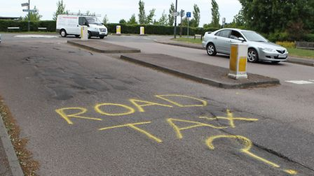 A protester frustrated with the state of repair has sprayed the words Road Tax? on Bedford road befo
