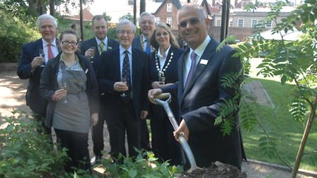 Malcolm Domb plants the tree watched by dignitaries and staff.