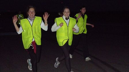 Charity runners pounding the runway at Stansted Airport in the dark of night.