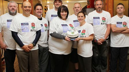 Volunteers helping to spruce up Stevenage Town Rugby Club with a cake donated by Fancy Cakes by Lind